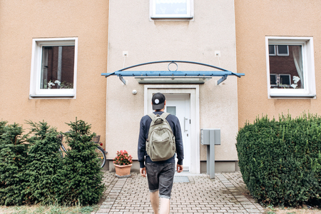 A tourist goes to the guesthouse or hostel in order to stay in a room that he booked or a student with a backpack returns home after his studies at the institute or on vacation. Stock Photo