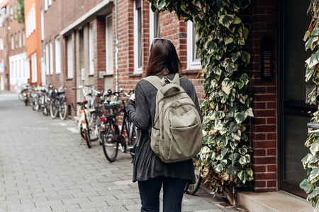 Tourist with a backpack is looking for booked online accommodation in an unfamiliar city. Or a student girl with a backpack is walking through the city.