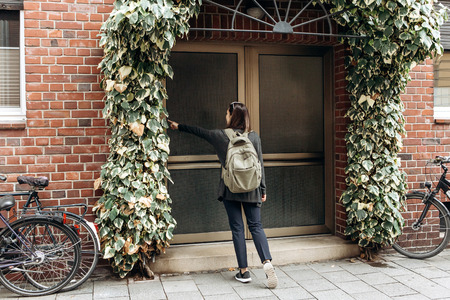 The tourist rings the doorbell to check in to the room he has booked or the student with the backpack returns home after classes at the institute or on vacation. Banque d'images - 109708922