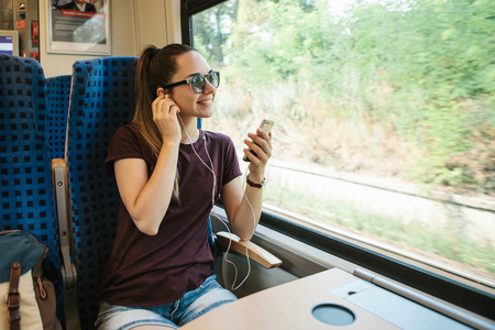 A young girl listens to a music or podcast while traveling in a train. Stock Photo