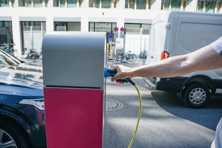 Close-up of a hand inserts a special cord or cable into an outdoor refueling station for refueling an electric car. Eco-friendly mode of transport. Imagens