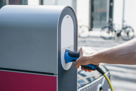 Close-up of a hand inserts a special cord or cable into an outdoor refueling station for refueling an electric car. Eco-friendly mode of transport. Reklamní fotografie