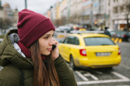 Young beautiful girl on the street in Prague calls a taxi or she goes about her business and talking on the phone. Winter time. City lifestyle. Stock Photo