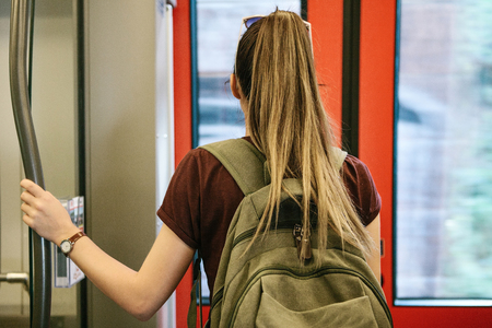 Tourist girl or student with a backpack waiting for the train to stop to go outside.