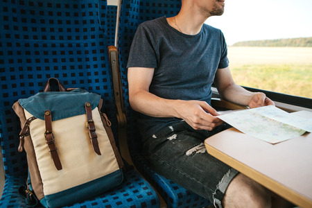 A tourist or a guy or a student with a backpack moves by train. He holds a map in his hands and looks out the window while the train is moving. Standard-Bild