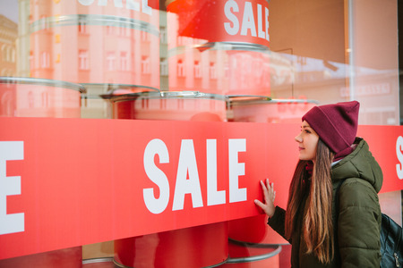 The girl at the storefront with a sale. Time of off-season and winter sales, Black Friday and Cyber Monday. Stock Photo
