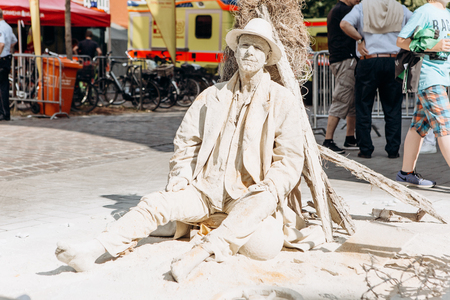 Germany, Muenster, October 5, 2018: A street artist performs living statue covered with dried mud, as if it were in a desert. Redactioneel