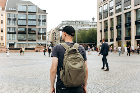 Tourist man with backpack or student in Leipzig Square in Germany admiring beautiful buildings or architecture. Traveling in Germany. Stok Fotoğraf