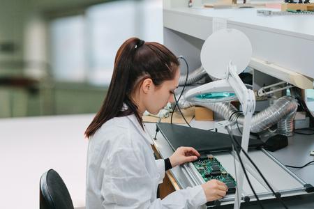 Un tecnico donna controlla una scheda di computer in una fabbrica. Occupazione professionale. Specialista altamente qualificato nel campo dell'assemblaggio di computer o della tecnologia informatica.