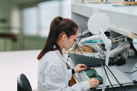 Una técnica revisa un tablero de computadora en una fábrica. Ocupación profesional. Especialista altamente cualificado en el campo del montaje de ordenadores o tecnología informática.