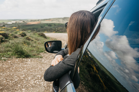 A girl driver or a female traveler inside the car looks out the window to the road ahead or unknown terrain while traveling.