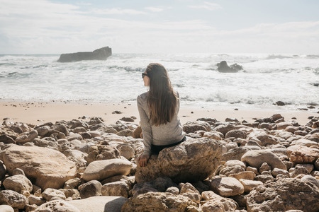 The girl in solitude admires a beautiful view of the Atlantic Ocean in Portugal. Search for soul or unity with nature.