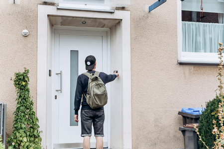 The tourist rings the doorbell to check in to the room he has booked or the student with the backpack returns home after classes at the institute or on vacation. Reklamní fotografie - 111999339