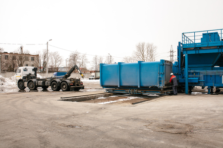 A special heavy machine loads a container with sorted waste at the plant for sorting waste to be transported to another plant for recycling.