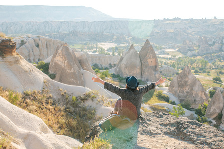 A girl sits on top of a mountain in solitude, admires the beautiful view of the natural landscape in Cappadocia in Turkey and raises her hands up showing how she is free and happy. Stock Photo