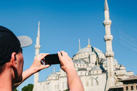 Tourist photographs the Blue Mosque in Istanbul in Turkey for memory.