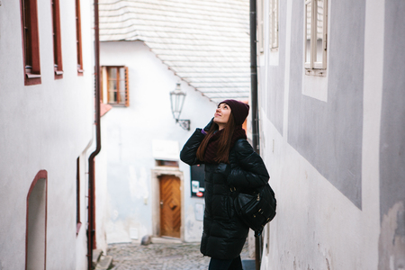Tourist girl on a beautiful street in Cesky Krumlov in the Czech Republic while traveling around the city is looking at sightseeing places or she is lost. Banque d'images - 114345572