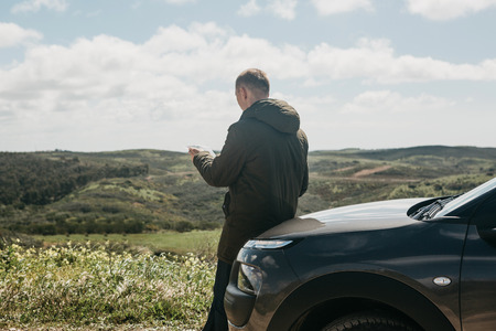 A tourist man next to the car looks at the map of the area for further travel. Stock Photo