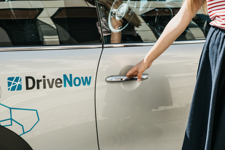 Germany, Berlin, September 05, 2018: A person opens the door of a rented BMW electric car from a company called DriveNow. Car rental takes place through a mobile application on a mobile phone.