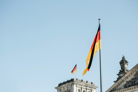 German flag over the Reichstag building in Berlin in Germany.