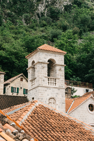 Beautiful view of the bell tower of the Orthodox Church in Kotor in Montenegro. Religious building. In the background is a mountain with trees. Standard-Bild