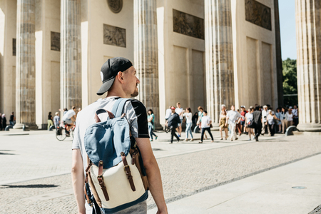 A tourist or a student with a backpack in Berlin in Germany visits the sights. Ahead is the Brandenburg Gate and unrecognizable blurred people. Stock Photo