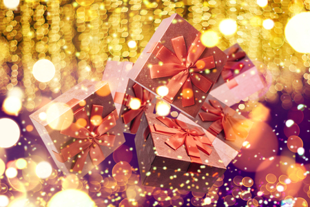 Many traditional gift boxes fall on a festive golden background. Holiday concept