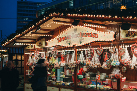 Berlin, December 25, 2017: Selling sweets and traditional gingerbread in the evening at the Christmas market in Berlin. Decorated stall. Editorial