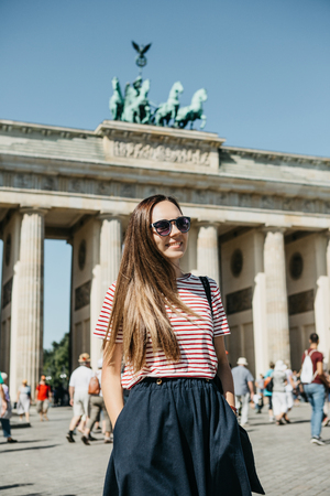 Portrait of a young beautiful positive smiling stylish tourist girl in Berlin in Germany. Brandenburg Gate and unrecognizable blurred people in the background.