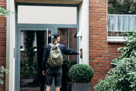The tourist rings the doorbell to check in to the room he has booked or the student with the backpack returns home after classes at the institute or on vacation. Banque d'images - 114417233