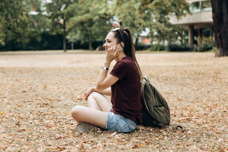 Beautiful young girl with a backpack sitting in the autumn park and talking on a mobile phone. Фото со стока