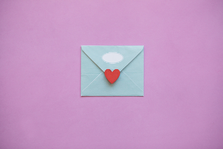 An envelope with a red heart for Valentines Day or for Womens Day or for the wedding. A joyful message or letter. Festive concept in minimal style.