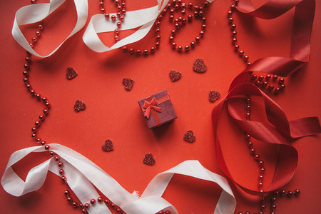 Red box with a gift on a festive background. Concept for Valentines Day or Womens Day or any holiday.