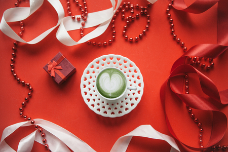 Delicious fresh green matcha coffee with a heart pattern on a red background with ribbons and beads. Near the red box with a gift. Concept for Valentines Day or Womens Day.