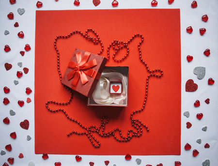 Red box and inside it is another small box with a heart. Concept for Valentines Day or Womens Day.