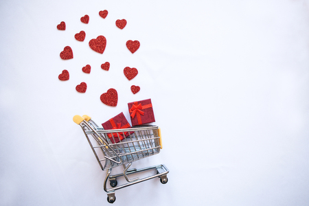 Shopping trolley with gift boxes and hearts. The concept of holiday sales Valentines Day and Womens Day.