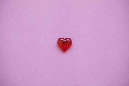 Red heart on a pink background. Concept for Valentines Day or Womens Day or the topic of health, life, donation and help. In minimal style.