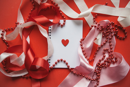 Festive background with ribbons and beads. In the middle is a notebook with a heart. Concept celebration of Valentines Day or another love event.