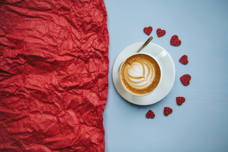 Fragrant delicious cappuccino on a blue and red background with many hearts. Concept for Valentines Day or Womens Day or another love event.