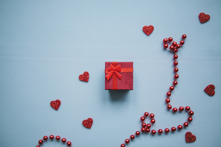 Festive background with a box with a gift and a lot of hearts and beads. Concept for Valentines Day or Womens Day or another love event.