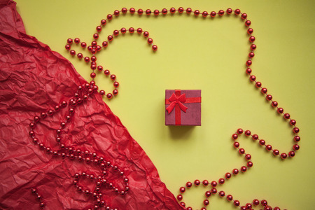 Red box with a gift on a festive background. Concept for Valentines Day or Womens Day or another love event.