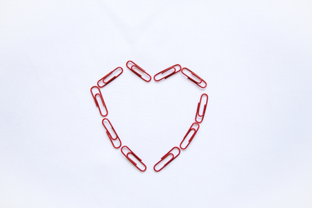 Paper clips laid out in the shape of a heart on a white background. Valentines Day celebration concept in minimal style.