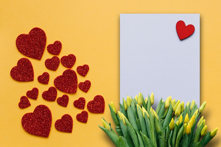 Blank sheet with red heart for text or write. Near many red hearts and a bouquet of yellow tulips. Concept for Valentines Day or Womens Day or Mothers Day.