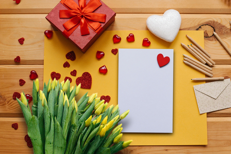 Blank sheet with red heart for text or write. Near an envelope to send and a box with a gift and a bouquet of yellow tulips. Concept for Valentines Day or Womens Day or Mothers Day.