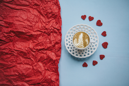 A cup of fresh flavored cappuccino coffee on a festive background with many hearts. Next to a red background there is a place for text. Celebration of Valentines Day or Womens Day or other love event.