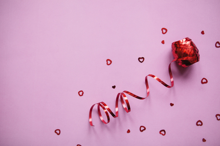 Red ribbon and many little hearts. Valentine's Day celebration concept in minimal style. Holiday items.