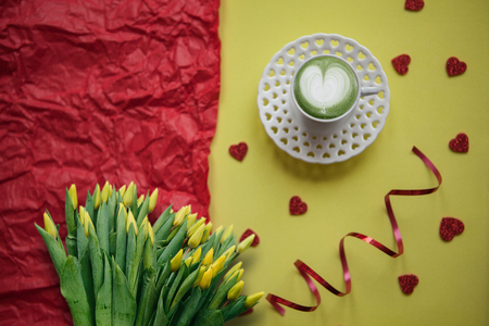 A cup with a tasty and aromatic morning matcha latte coffee on a festive background with many hearts. Next is a bouquet of yellow tulips.