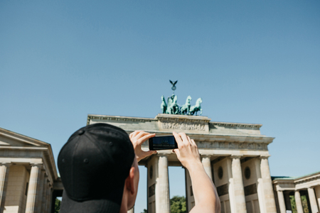 Tourist photographs on a mobile phone the Brandenburg Gate in Berlin in Germany. Sightseeing.