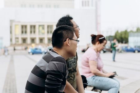 Germany, Leipzig, September 6, 2018: Asian tourists or immigrants sit in the city park and admire the sights. Editorial