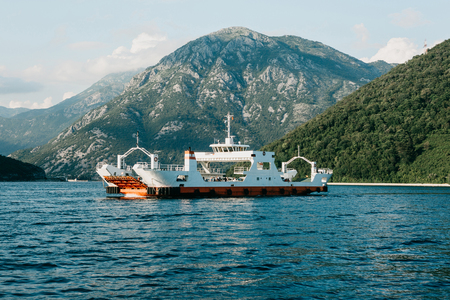 Ferry to transport vehicles and people crosses the bay in Montenegro. Imagens - 115670430